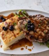 Mustard-Fennel Marinated Pork Porterhouse, Potato Gratin, Mustard Jus, Charred Asparagus, Pickled Blueberries