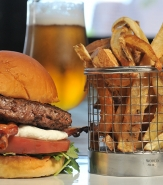 Brasserie Burger - ½ lb. Stilton Sirloin Burger, Bacon Sheet, Arugula, Onion Jam, Tomato, Brioche Bun